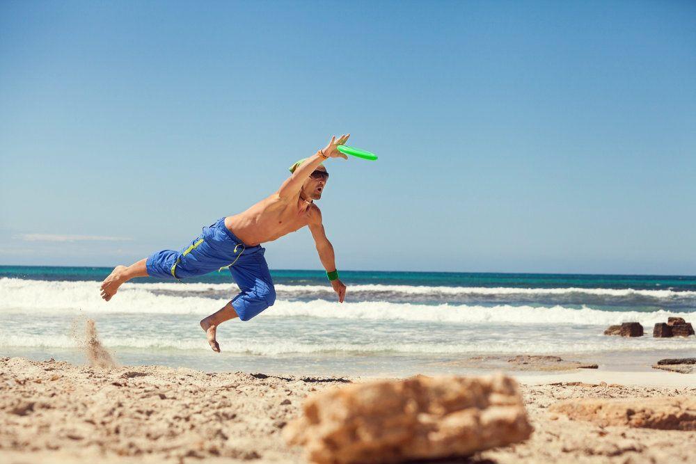 Jugar al frisbee en la playa